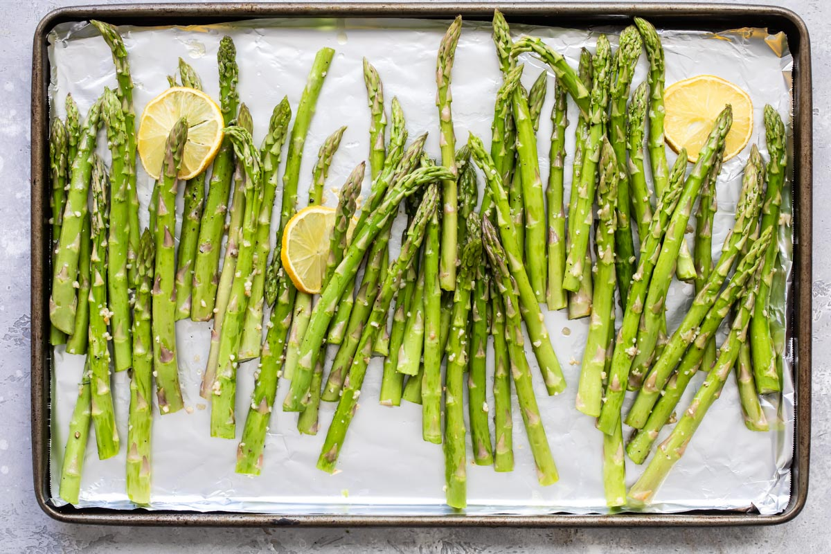 Raw asparagus on a rimmed baking sheet with lemon slices.