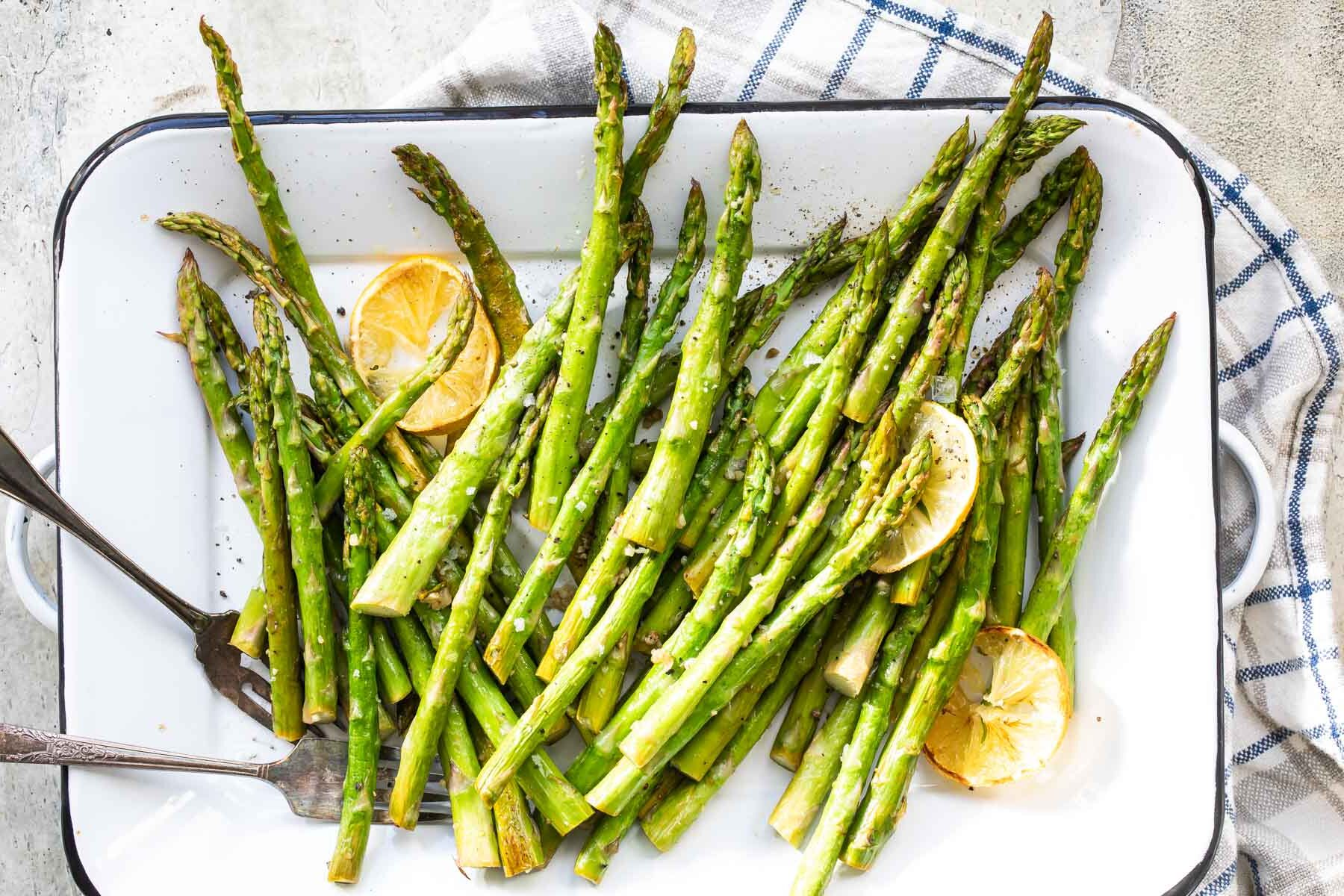 Roasted asparagus on a rimmed baking sheet with lemon slices.