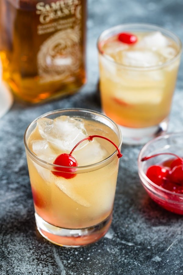 A side shot of a whiskey sour cocktail garnished with a cherry.