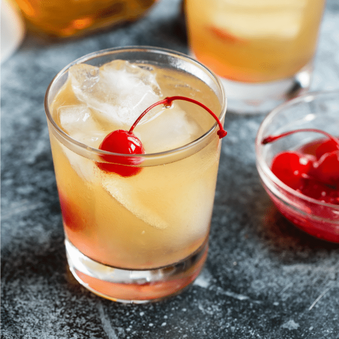 Whiskey sour cocktail garnished with a cherry.