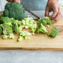 Broccoli being cut on a wooden cutting board.