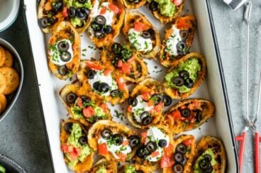 Baked potato skins in a white baking dish.