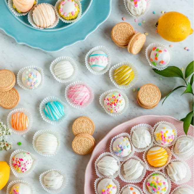 These Lemon Cookie Balls are inspired by seasonal lemon-flavored Oreos.  They are made like traditional Oreo Cookie balls but taste lighter and brighter, like lemon cheesecake. These balls require only 3 ingredients, but optional the decorations will add a pop of color to your holiday table!