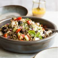 Mediterranean lentil salad in a grey bowl.