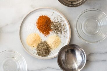 Rotisserie chicken seasoning spices on a white plate.
