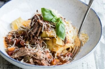 Slow cooker beef ragu with pappardelle in a white bowl with a silver fork.