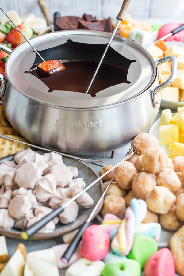 Chocolate fondue in a silver pot with various items to dip.