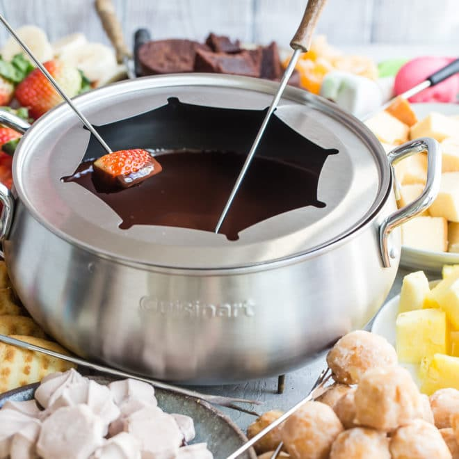 Chocolate fondue in a silver fondue pot.