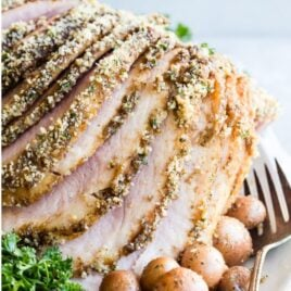 Baked ham with crumb topping on a white plate with a fork resting on the plate.