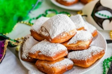 Beignets dusted with powdered sugar on a white plate.