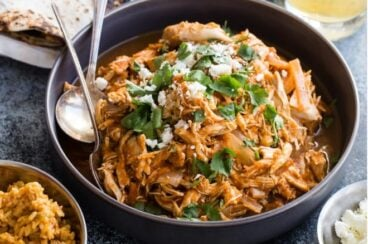 Chicken tinga in a bowl with tortilla shells and lettuce nearby.