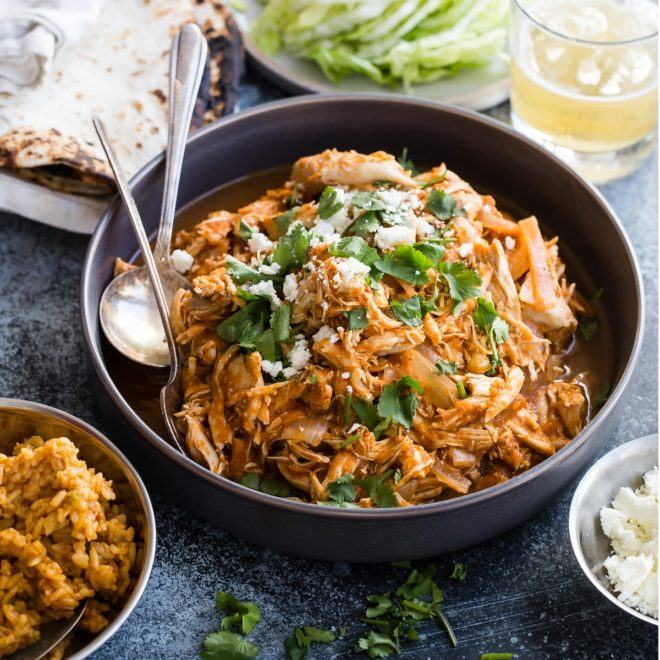 Chicken tinga in a black serving bowl.