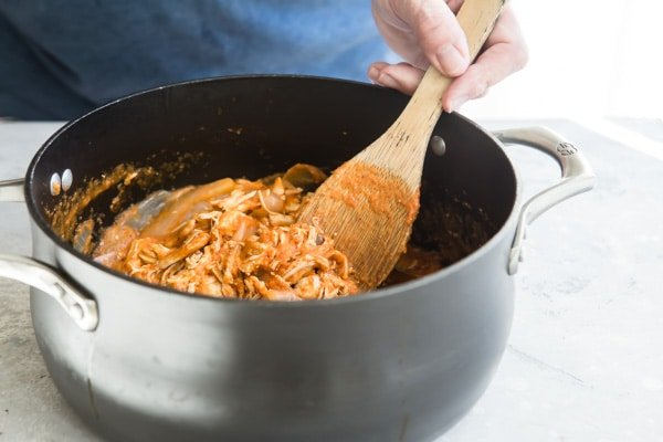 Tinga sauce being stirred in to a saucepan with chicken.