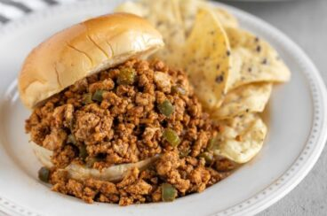 A chipotle chicken sloppy joe on a white plate with tortilla chips.