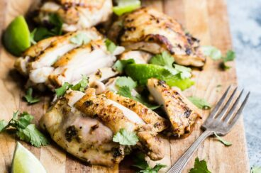 Slices of cilantro lime chicken on a wooden cutting board.