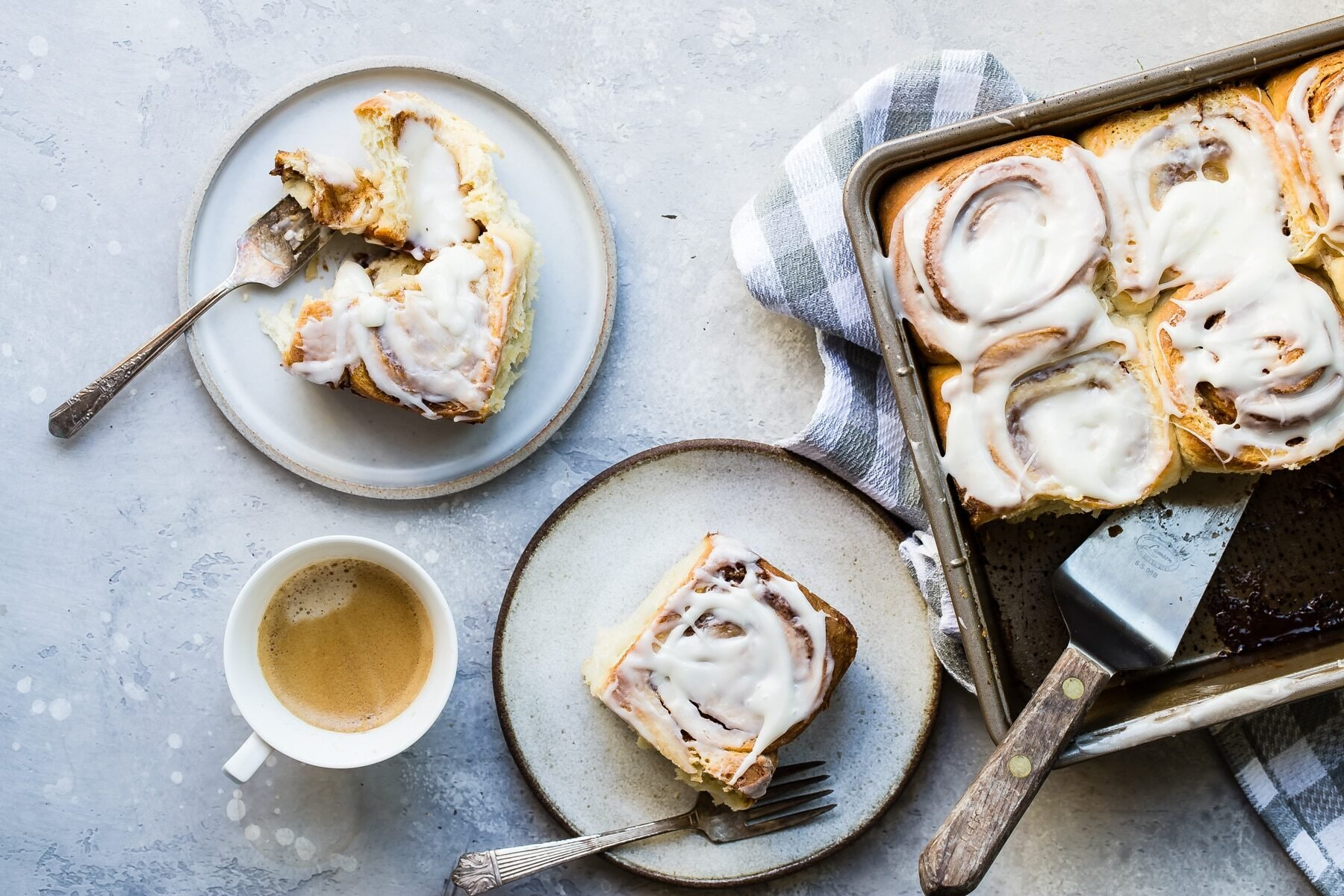 Cinnamon rolls on a plate next to pan of them.