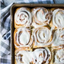 Homemade cinnamon rolls on a baking sheet.