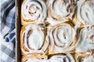 Homemade cinnamon rolls on a baking sheet.