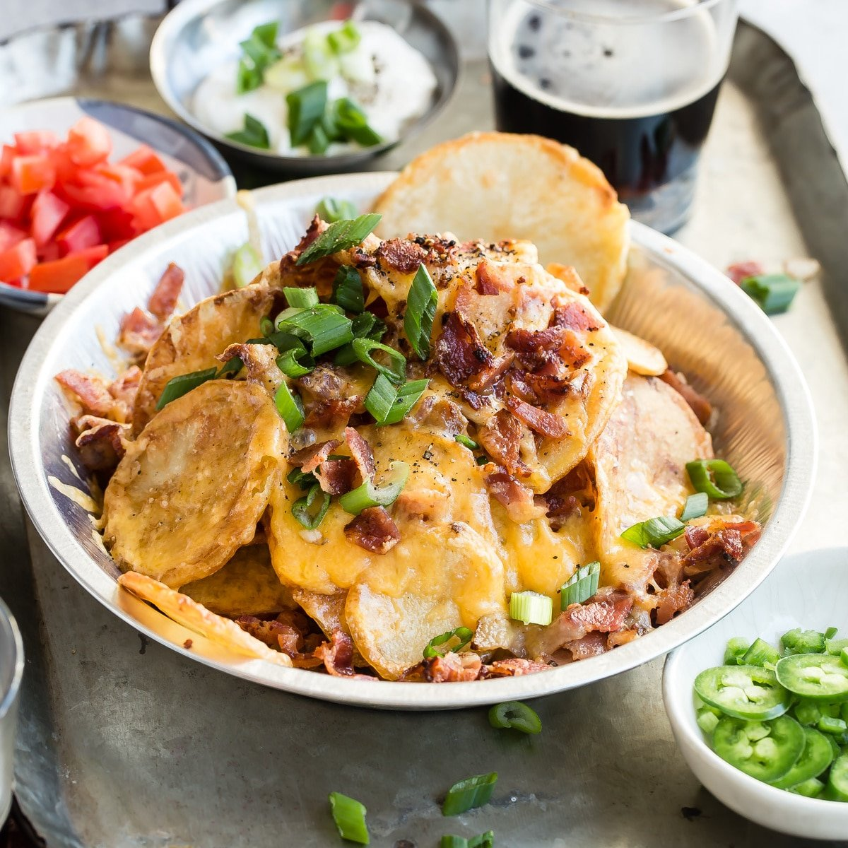 A platter of Irish Nachos is pub food at its finest; all the best parts of a loaded baked potato and Tex-Mex nacho ingredients come together in one glorious bite. This recipe is American fusion food at its best!