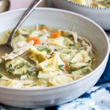 Slow cooker chicken tortellini soup in a white bowl.