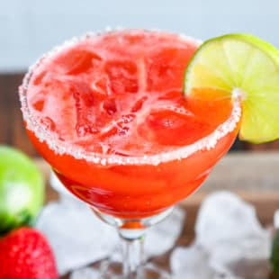 A closeup angled shot of a strawberry margarita in a clear stemmed glass.