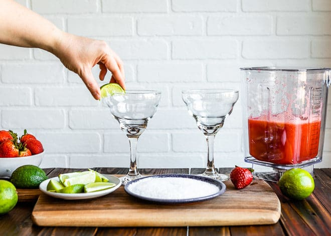 A person setting a lime on a margarita glass.
