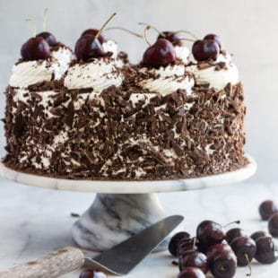Black forest cake on a white and black marbled cake stand.