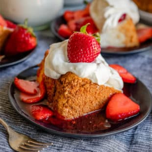 A closeup side shot of a slice of angel food cake with how to make whipped cream and strawberries on a black plate.