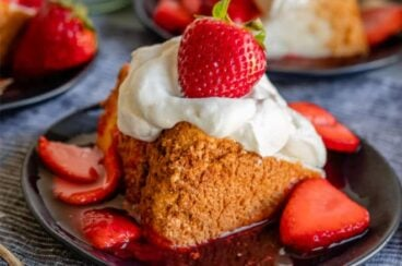 A slice of angel food cake with how to make whipped cream and strawberries on a black plate.