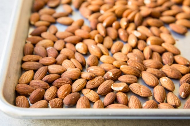 An overhead shot of whole almonds on a roasting pan.