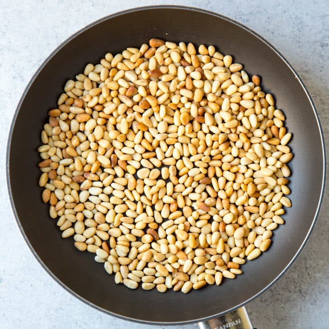 An overhead shot of pine nuts in a skillet.