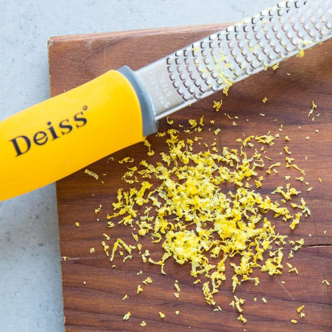 A zester sitting on top of a wooden cutting board, with Lemon and Zest