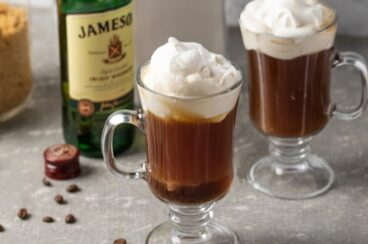Irish coffee in two clear coffee mugs.