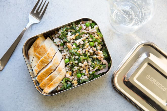 Israeli Couscous Salad in a metal lunch box with bread.