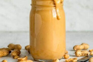 Homemade peanut butter in a clear jar.