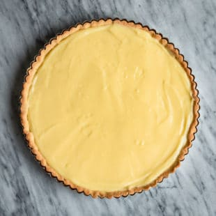 An overhead shot of how to make pastry cream in a baked tart crust.