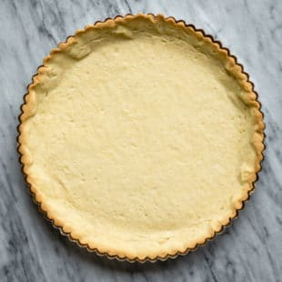 A baked tart crust in a tart pan.