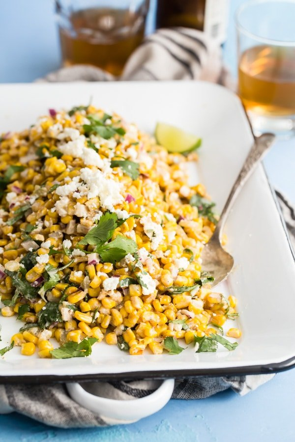 Mexican corn salad on a white rectangular platter.