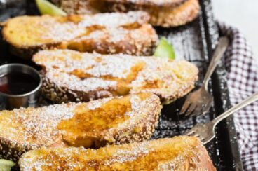 Challah french toast covered with powdered sugar and syrup on a black cookie sheet.
