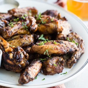 A closeup angled shot of smoked chicken wings on a white platter.