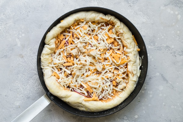 An overhead picture of an uncooked pizza crust with sauce and cheese in a cast iron skillet.