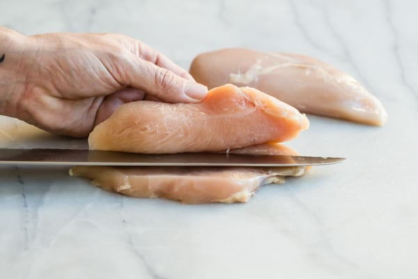 Someone slicing a piece of chicken in half with a knife.