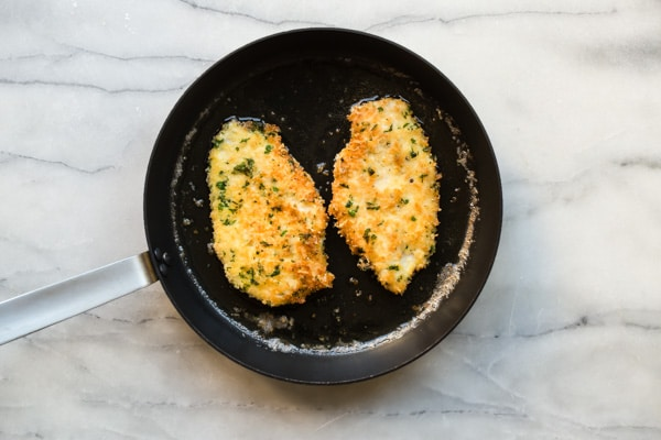Two pieces of chicken piccata cooking on a black skillet.
