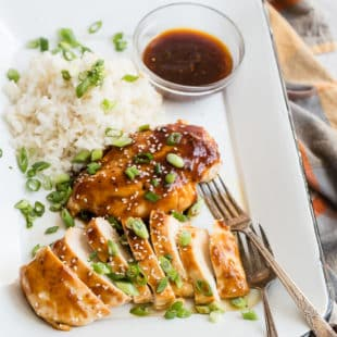 Honey garlic chicken with white rice on a white platter.