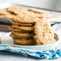 Oatmeal scotchies stacked on a white plate.