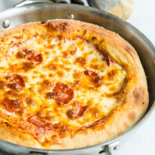 Pepperoni pizza in a silver skillet.