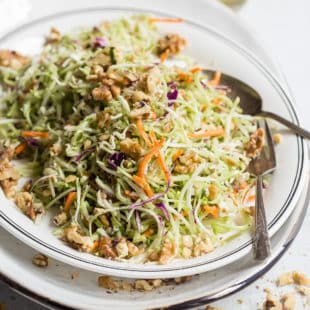 A closeup angled shot of broccoli slaw on a white platter.