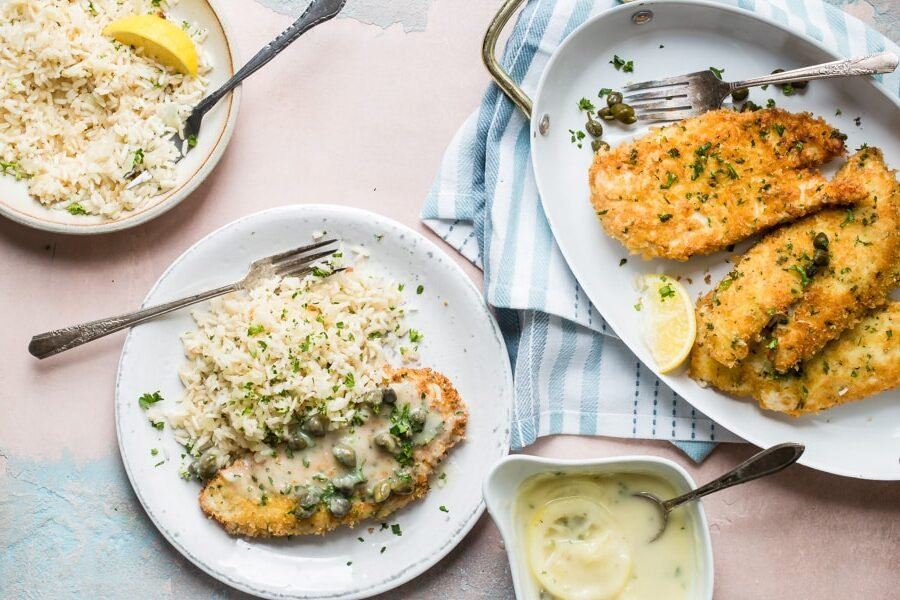 Chicken piccata in a dish and a serving of chicken piccata on a white plate with rice.