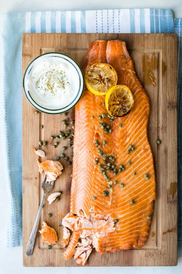 Smoked salmon on a cutting board with lemons and capers as a garnish.