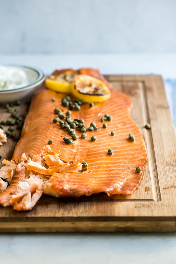 Smoked salmon on a platter with capers and lemon as a garnish.